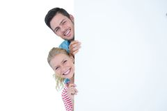 Smiling young couple hiding behind a blank sign. On whit background Royalty Free Stock Images