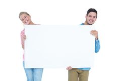Smiling young couple holding a blank sign Royalty Free Stock Photography