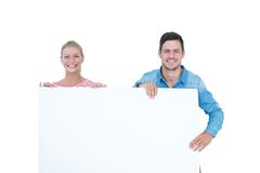 Smiling young couple holding a blank sign Stock Images