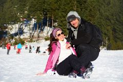 Smiling young couple hugging snowman. In a snowy mountain royalty free stock photography