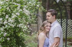 Smiling young couple hugging under flower arch royalty free stock photos