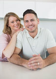 Smiling young couple at kitchen counter Royalty Free Stock Images