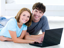 Smiling young couple with laptop Stock Image