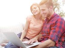 Smiling young couple with laptop sitting on the couch. On blurred background Royalty Free Stock Photos