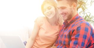 Smiling young couple with laptop sitting on the couch. On blurred background Royalty Free Stock Photography