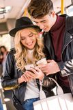 Smiling young couple in leather jackets using smartphone in public. Transport Stock Photo