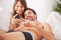 Smiling young couple looking smartphone in bed Stock Photography