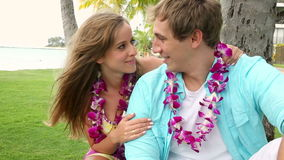 Smiling Young Couple In Love with Lei, Sitting And Hugging under palm tree. Portrait of a happy and romantic couple wearing flower Lei on beach Oahu Hawaii stock footage