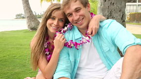 Smiling Young Couple In Love with Lei, Sitting And Hugging under palm tree. Portrait of a happy and romantic young couple wearing flower Lei on beach Oahu Hawaii stock footage