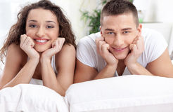 Smiling young couple in love lying in bed Stock Photo