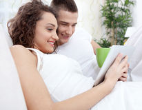 Smiling young couple lying in the bed and use tablet pc Stock Image
