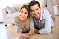 Smiling young couple lying on the floor Stock Photos