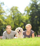 Smiling young couple lying on a grass and hugging a dog in a par Stock Photography