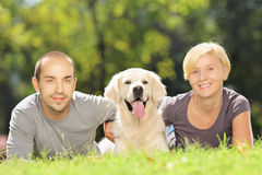 Smiling young couple lying on grass and hugging a dog in park Stock Photography