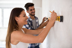 Smiling young couple measuring wall with level tool, renovation Stock Images