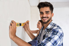 Smiling young couple measuring wall with level tool, renovation Stock Photography