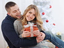 Smiling young couple near Christmas tree with gift Stock Photo