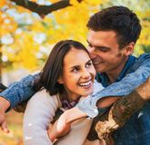 Smiling young couple outdoors in autumn having fun t Stock Image