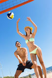 Smiling young couple playing volleyball Stock Photography
