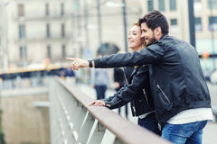 Smiling young couple pointing something on an autumns day. Royalty Free Stock Photos