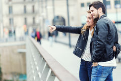 Smiling young couple pointing something on an autumns day. Royalty Free Stock Photography