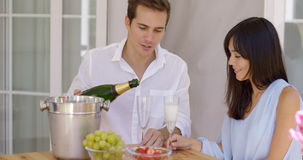 Smiling young couple pouring champagne to drink Stock Image