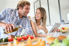 Smiling young couple preparing supper Stock Photography