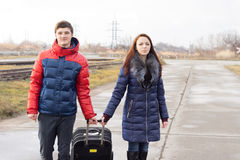 Smiling young couple pulling along a suitcase Stock Images