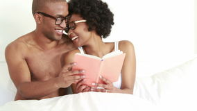 Smiling young couple reading book together stock video footage