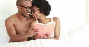 Smiling young couple reading book together stock footage