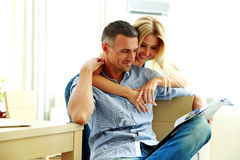 Smiling young couple reading magazine Stock Image
