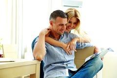 Smiling young couple reading magazine stock image