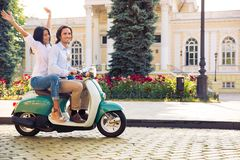 Smiling young couple riding on the scooter Royalty Free Stock Images