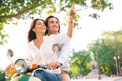 Smiling young couple on scooter together Royalty Free Stock Image