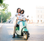 Smiling young couple on scooter Royalty Free Stock Images