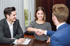 Smiling young couple shaking hands with an insurance agent Royalty Free Stock Photos