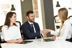 Smiling young couple shaking hands with an insurance agent. Or investment adviser. Three people meeting in an office reaching an agreement Royalty Free Stock Photos