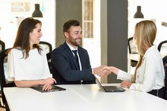 Smiling young couple shaking hands with an insurance agent. Or investment adviser. Three people meeting in an office reaching an agreement Stock Photo