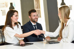 Smiling young couple shaking hands with an insurance agent. Or investment adviser. Three people meeting in an office reaching an agreement Royalty Free Stock Photo