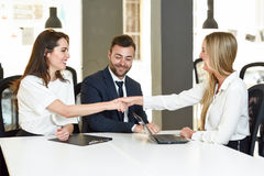 Smiling young couple shaking hands with an insurance agent. Or investment adviser. Three people meeting in an office reaching an agreement Stock Images
