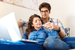 Smiling young couple shopping online over the laptop. Smiling young couple shopping online over the laptop in their home royalty free stock photography