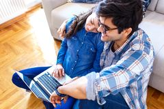 Smiling young couple shopping online over the laptop. Smiling young couple shopping online over the laptop in their home royalty free stock images