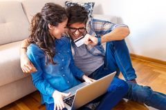 Smiling young couple shopping online over the laptop. Smiling young couple shopping online over the laptop in their home royalty free stock photos