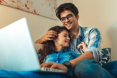 Smiling young couple shopping online over the laptop. Smiling young couple shopping online over the laptop in their home royalty free stock photo