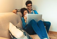 Smiling young couple shopping online over the laptop. Smiling young couple shopping online over the laptop in their home stock photos