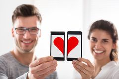 Couple Showing Heart Shape On Cell Phone Royalty Free Stock Images
