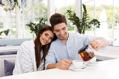 Smiling young couple sitting at the cafe table. Drinking tea stock photos