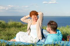 Smiling young couple sitting on grass near of water. Man laying on grass looking on happy woman stock photo