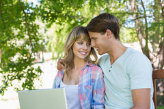 Smiling young couple sitting on park bench using laptop Stock Image