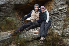 Smiling young couple sitting on rock while on a hike Royalty Free Stock Image